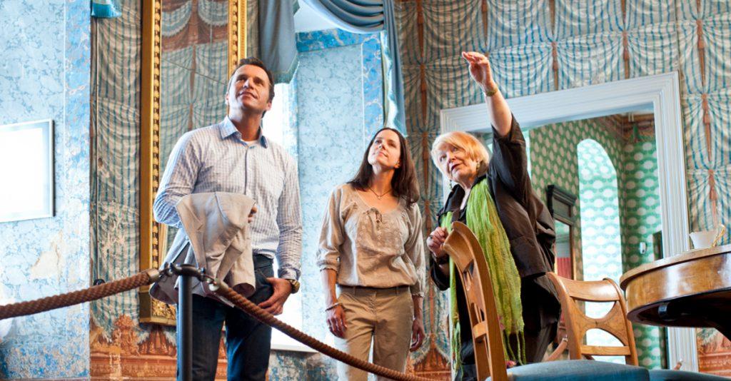 Betrachtung und Diskurs einer dreiköpfigen Gruppe in buntem Schlossraum